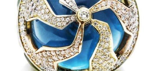 Кольцо Пангея от Kara Ross состоит из пяти подвижных частей, которые перемещаются независимо друг от друга над голубым топазом огранки кабошон и складываются как паззл